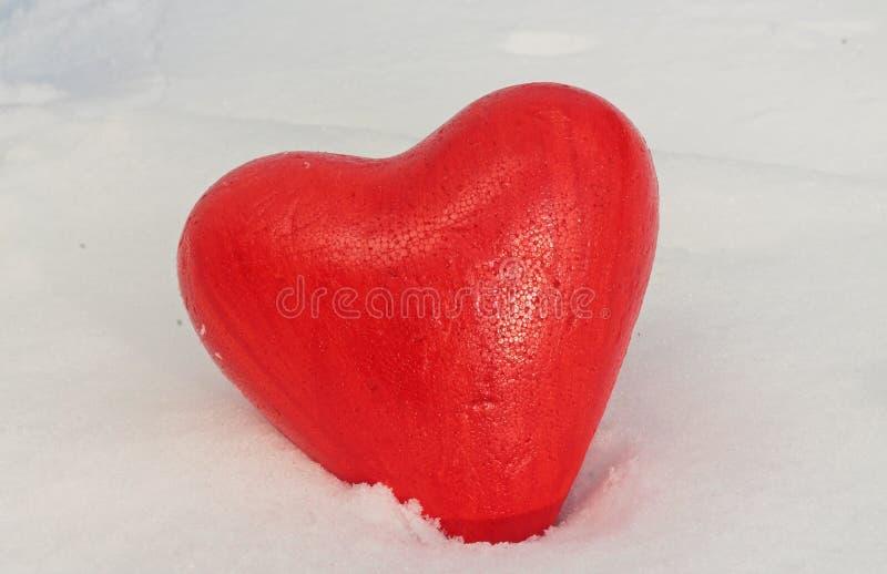 Coeur rouge dans la neige photos stock