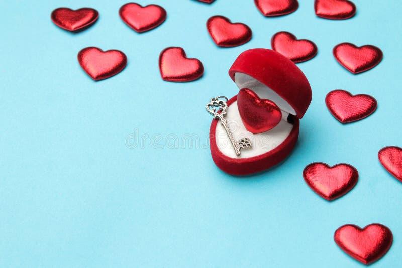 Coeur rouge dans un boîte-cadeau rouge avec une clé et petits coeurs sur un plan rapproché bleu lumineux de fond L'espace pour le photo libre de droits