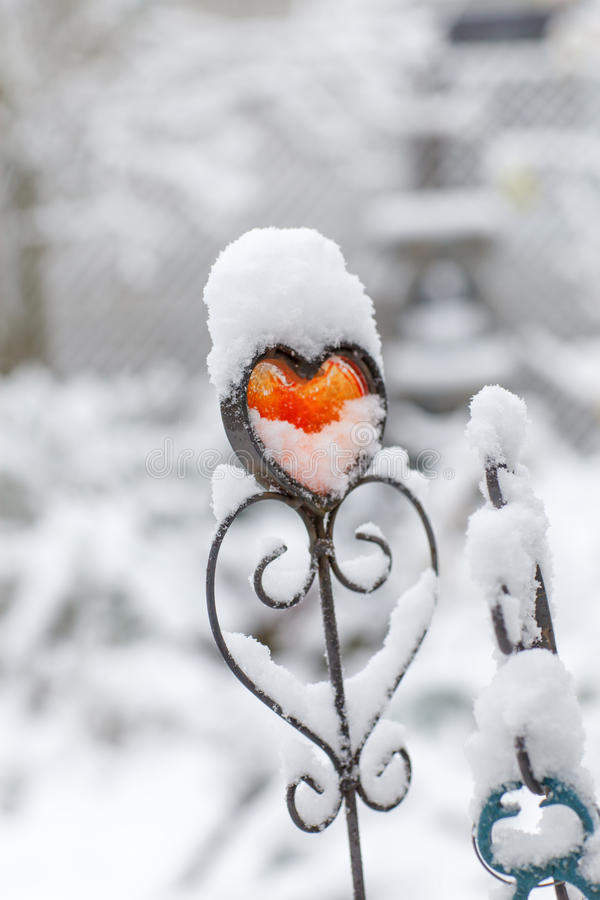Coeur rouge de fer avec la neige dehors photo stock