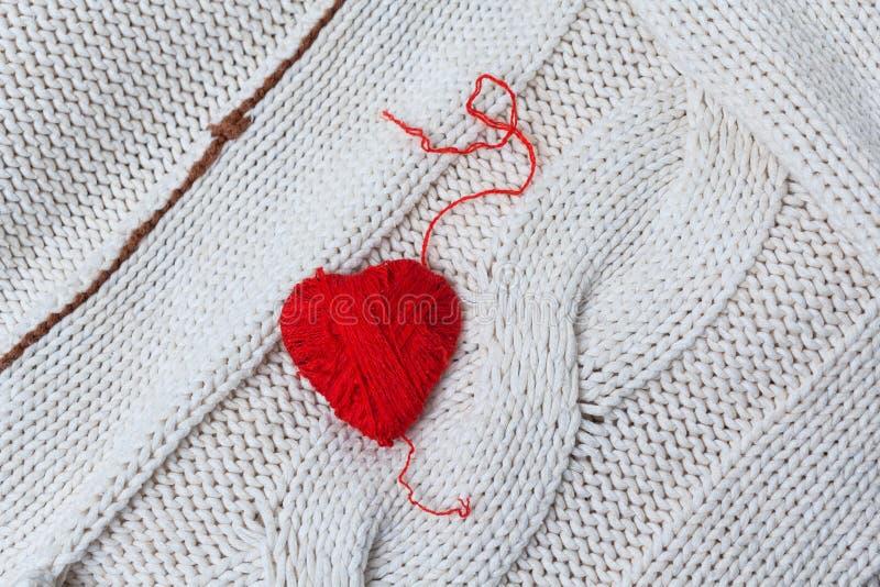 Coeur rouge de fil rouge sur un fond des chandails tricotés photo libre de droits