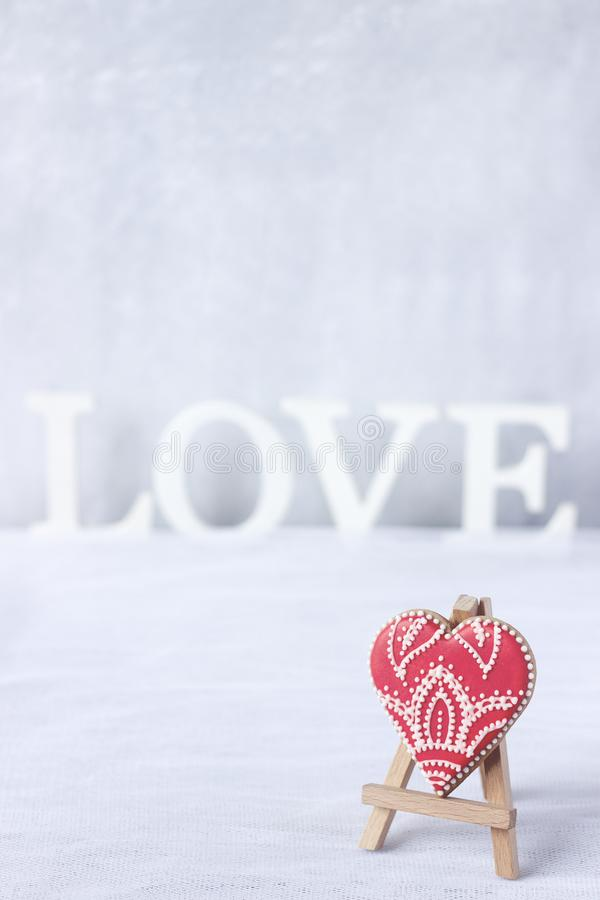 Coeur rouge de pain d'épice sur un fond blanc avec un amour d'inscription Carte postale au jour de St Valentine photographie stock