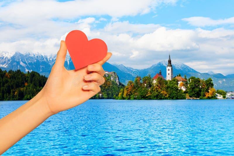 Coeur rouge de prise de main au-dessus d'île saignée en Slovénie images libres de droits