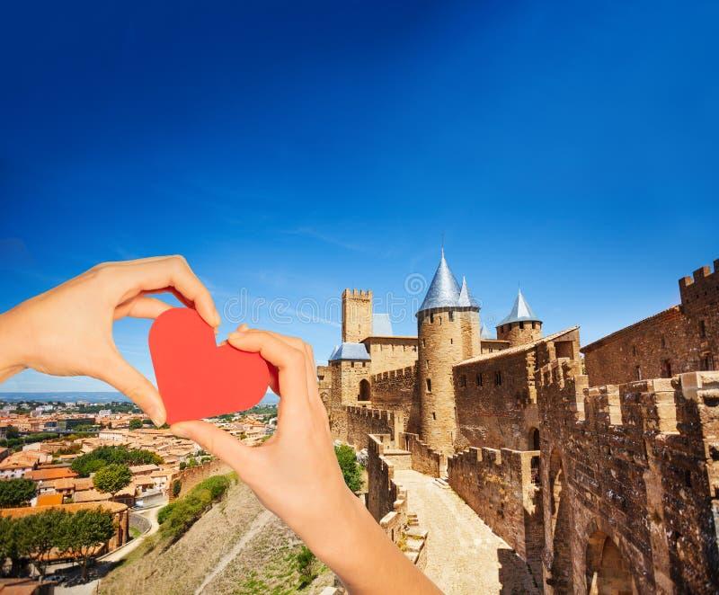 Coeur rouge de prise de main au-dessus des murs de ville de Carcassonne photo libre de droits