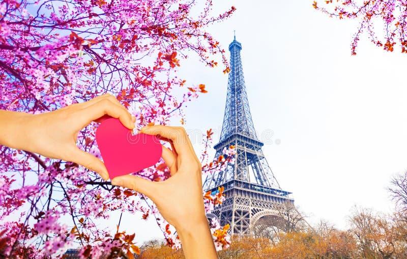 Coeur rouge de prise de main au-dessus de Tour Eiffel image stock