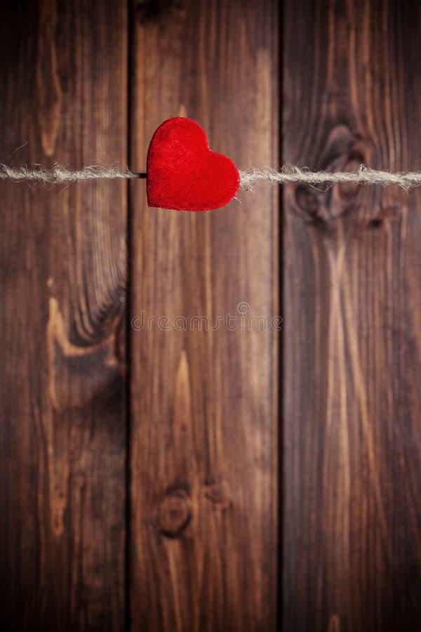 Coeur rouge de tissu accrochant sur la corde à linge photos stock