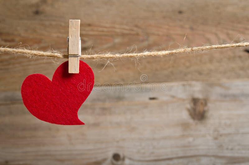 Coeur rouge de tissu accrochant sur la corde à linge photographie stock libre de droits