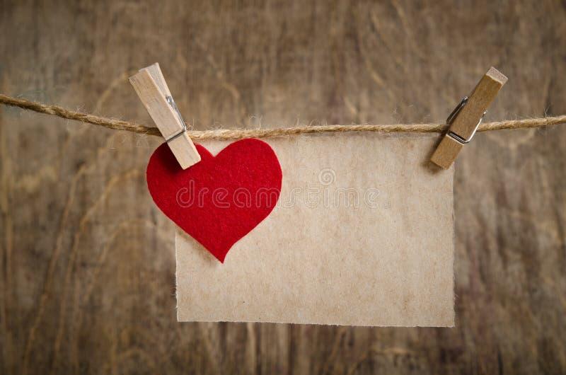 Coeur rouge de tissu avec la feuille de la pose de papier peint sur la corde à linge photographie stock libre de droits