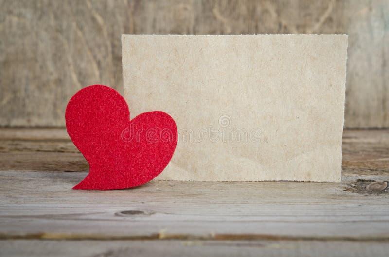 Coeur rouge de tissu avec la feuille de papier photos stock