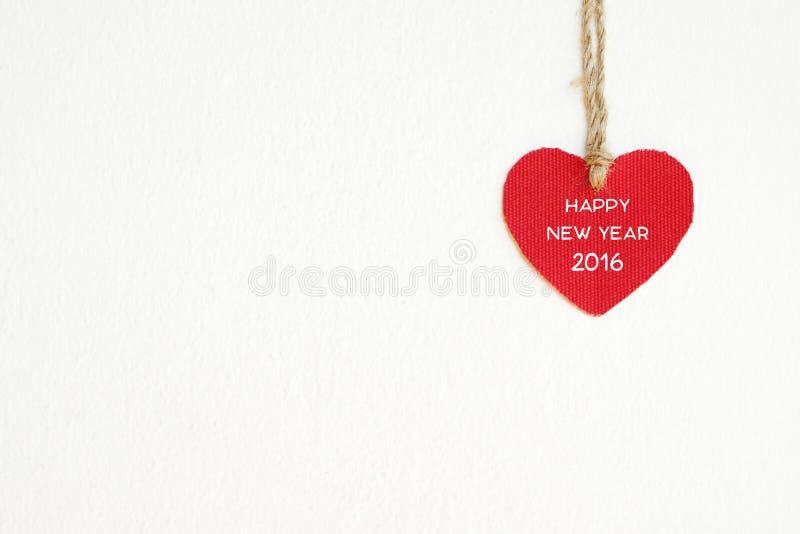Coeur rouge de tissu avec le mot de la bonne année 2016 accrochant sur le Cl image libre de droits