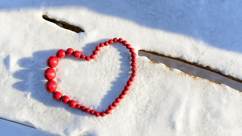 Coeur rouge des perles sur le fond en bois et de neige images stock