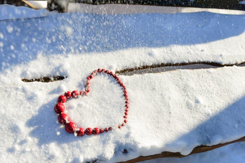 Coeur rouge des perles sur le fond en bois et de neige Jour du `s de Valentine photo libre de droits