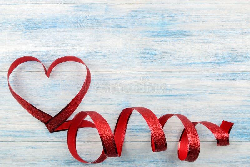 Coeur rouge des rubans sur un fond en bois bleu Place pour le texte Jour du `s de Valentine photos libres de droits