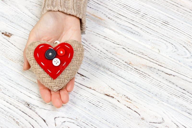 Coeur rouge en plan rapproché de mains sur le fond en bois Concept de jour du ` s de Valentine avec le copyspace image libre de droits