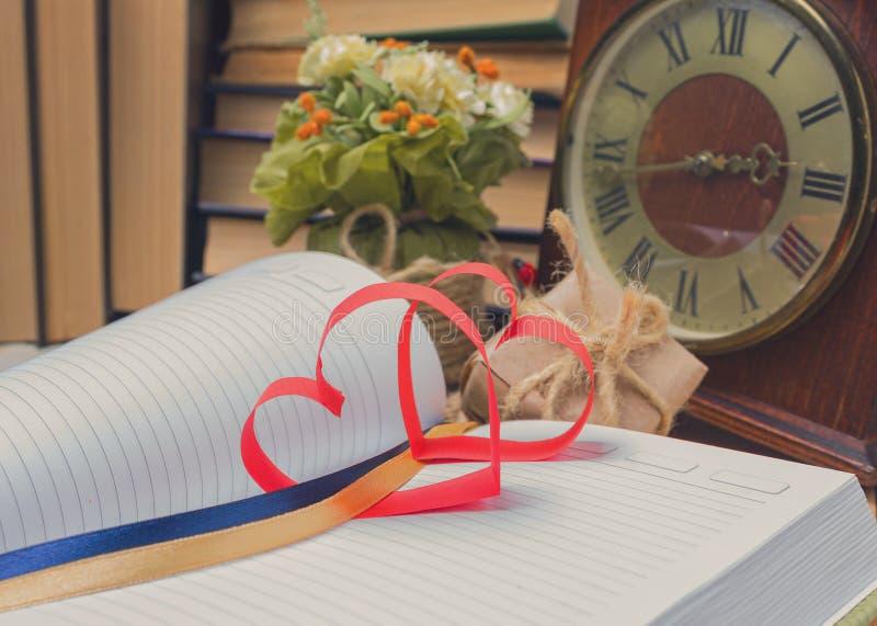 Coeur rouge fait de carnet et horloge de papier photo stock