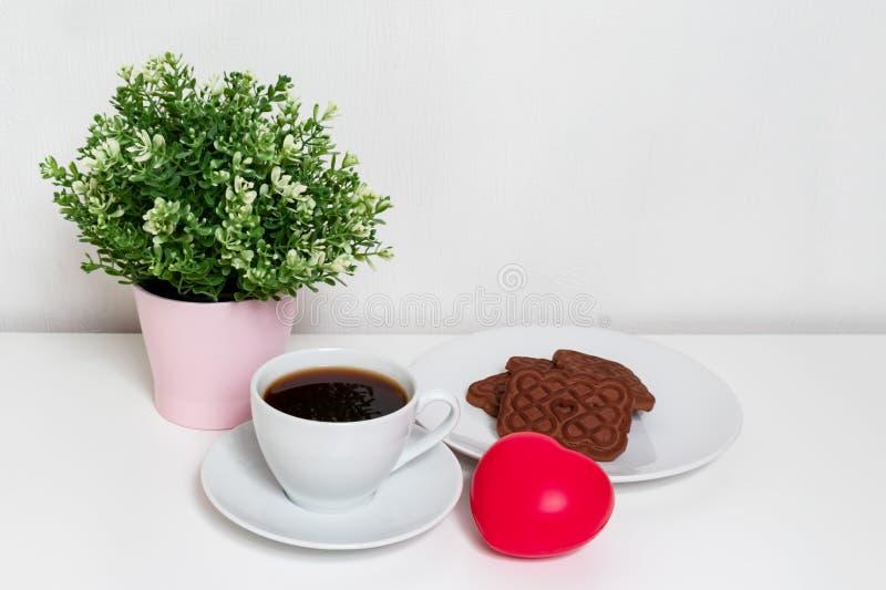 Coeur rouge se trouvant sur la table blanche près d'une tasse de café et de concept de jour de biscuits, de ressort et de valenti photographie stock
