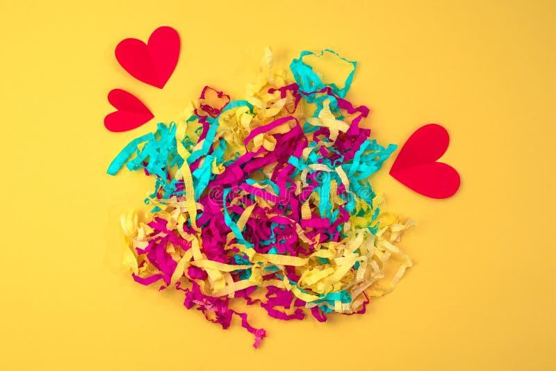 Coeur rouge serpentin coloré lumineux sur un concept jaune coloré de fond de Valentine& x27 ; jour de s photographie stock libre de droits