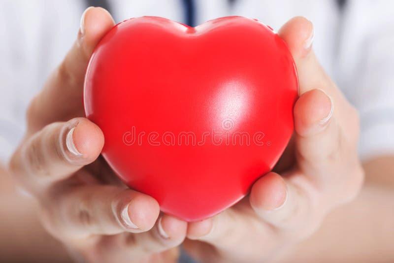 Coeur rouge tenu par un docteur féminin. image stock