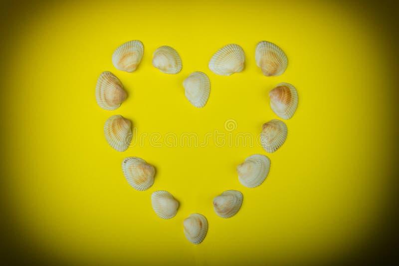 Coeur symbolique fait à partir des coquillages se trouvant sur le fond jaune photos libres de droits