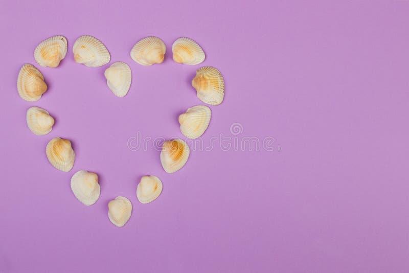 Coeur symbolique fait à partir des coquillages se trouvant sur le fond pourpre images stock