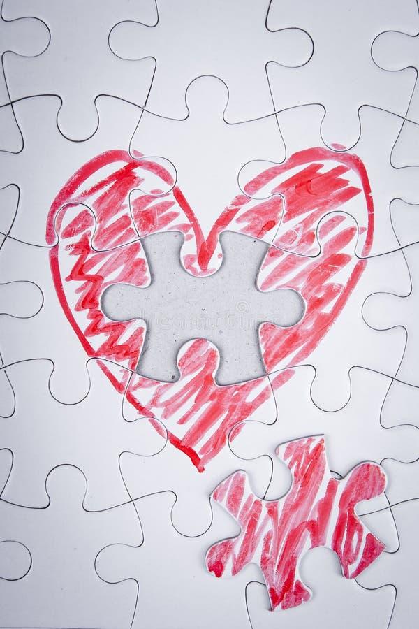 Coeur tiré par la main dans un puzzle photographie stock libre de droits
