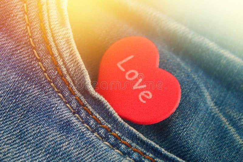 Coeur - un symbole des piaulements d'amour hors de la poche de pantalons de jeans Le concept du jour des amants Jour de rue Valen image stock