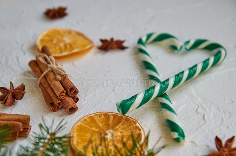 Coeur vert des cônes de sucrerie avec des épices - étoiles d'anis, oranges sèches, bâtons de cannelle sur le fond blanc Sucreries images stock