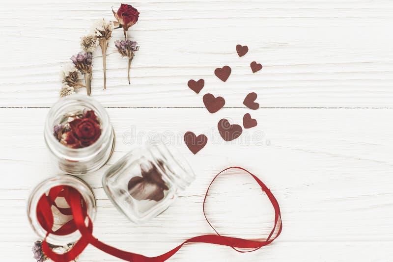 Coeurs élégants dans le pot et les roses en verre sur le Ba en bois rustique blanc images libres de droits