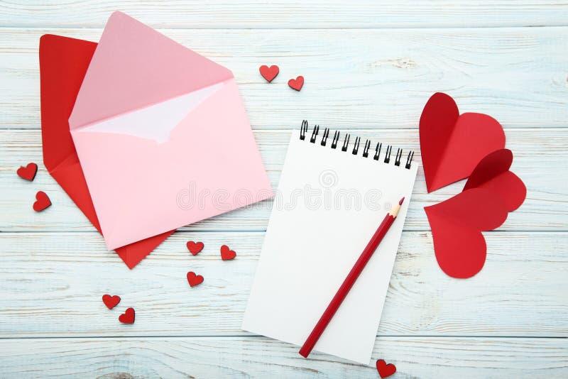 Coeurs avec les enveloppes, le carnet et le crayon images libres de droits