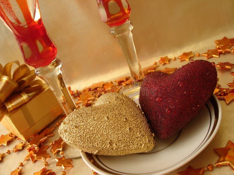 Coeurs, cadre de cadeau et glaces d'or et rouges sur la table de célébration images libres de droits