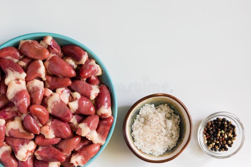 Coeurs crus frais de poulet sur le fond blanc Viandes d'organe, sel et poivre, faisant cuire des ingrédients image libre de droits