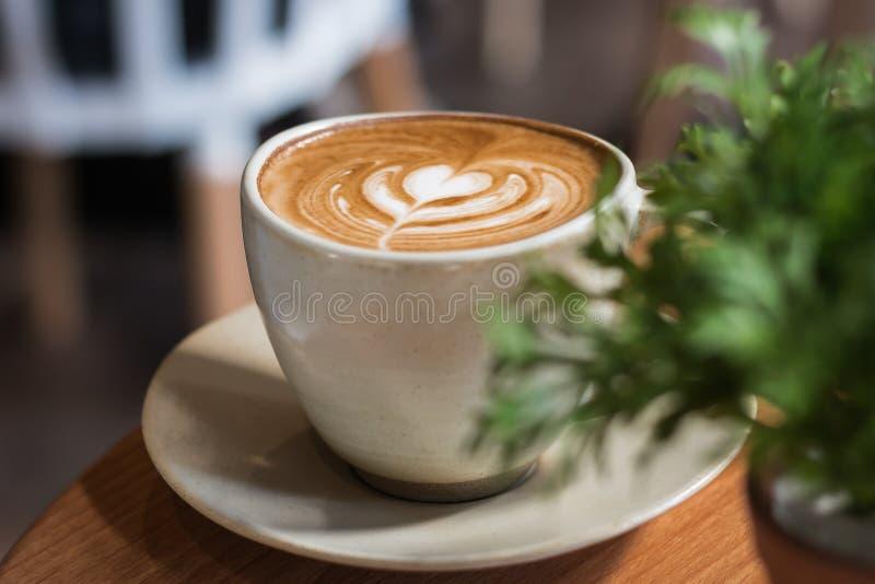 Coeurs de latte de café formés empilés sur le plancher en bois photo stock