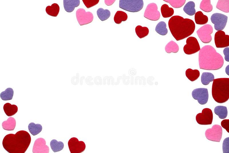 Coeurs dispersés rouges, de pourpre et de rose de feutre d'isolement sur un fond blanc, coin, frontière - valentines, amour photographie stock libre de droits