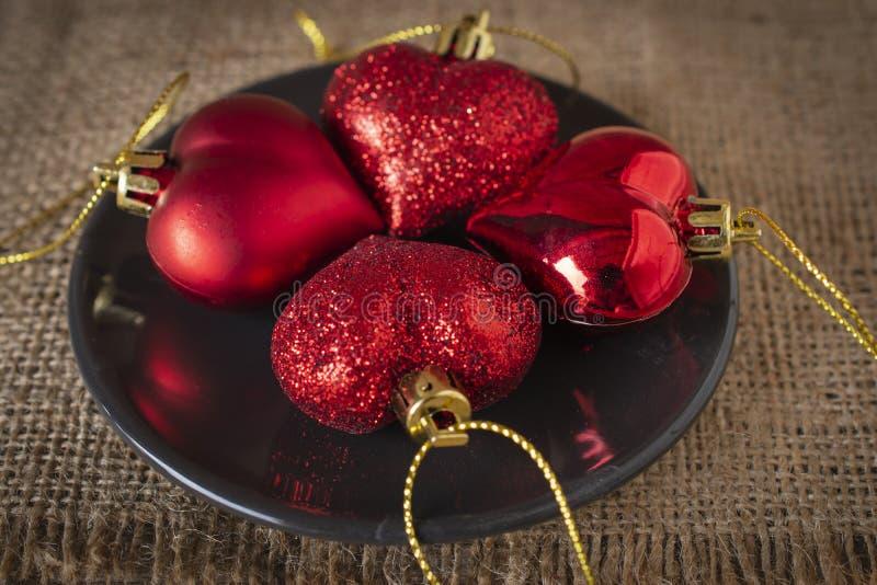 Coeurs en plastique rouges placés sur le plat noir et le sac image stock
