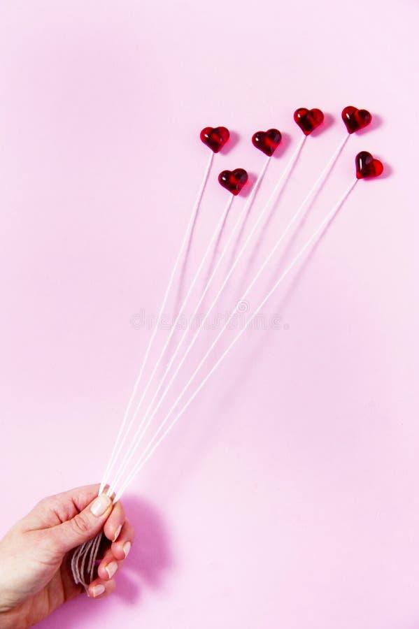 Coeurs en plastique sur un fond rose comme groupe de ballon, se tenant par une main du ` s de femme photos libres de droits