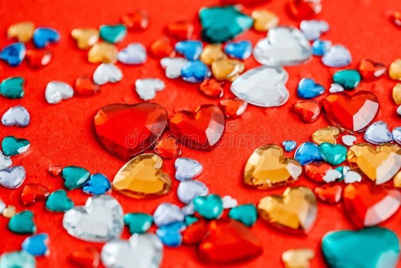 Coeurs en verre multicolores sur un fond rouge Le concept convient à l'histoire d'amour et à la Saint-Valentin photo libre de droits
