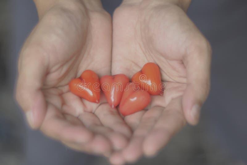 Coeurs en verre rouges dans des mains de l'homme Idée de soin de concept Fond de Saint-Valentin et de concept de santé, de médeci images stock