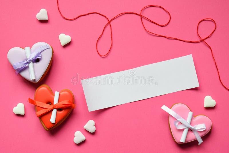 Coeurs faits maison de pain d'épice avec un papier vide pour votre texte sur le fond rose Coeurs de biscuits de Valentine Valenti photo stock