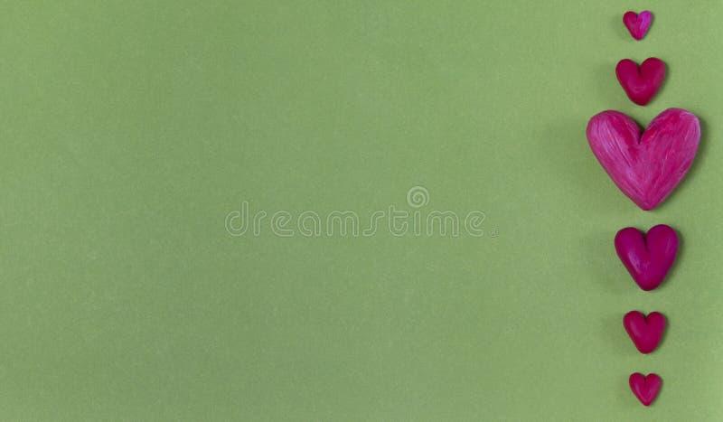 Coeurs rouges de pâte à modeler sur un fond vert clair images stock