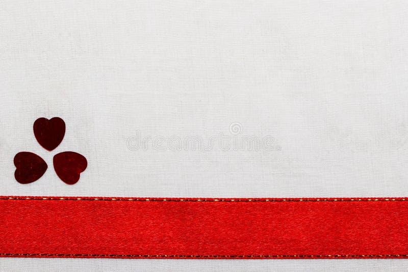 Coeurs rouges de ruban de satin sur le tissu blanc image libre de droits