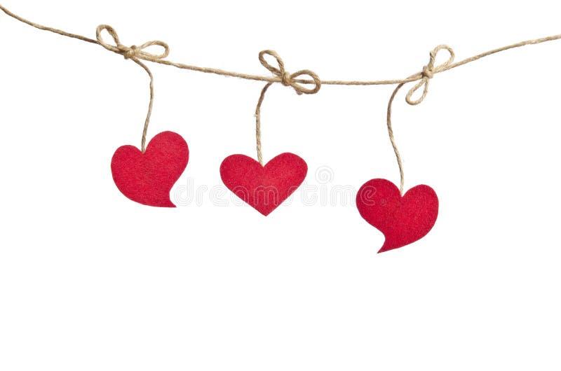 Coeurs rouges de tissu accrochant sur la corde à linge image stock