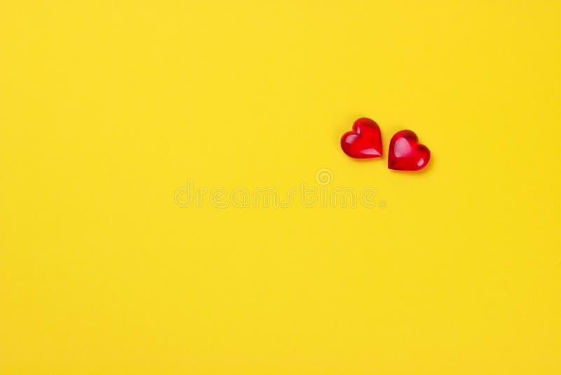 Coeurs rouges du concept deux de jour de valentines sur le fond jaune image stock