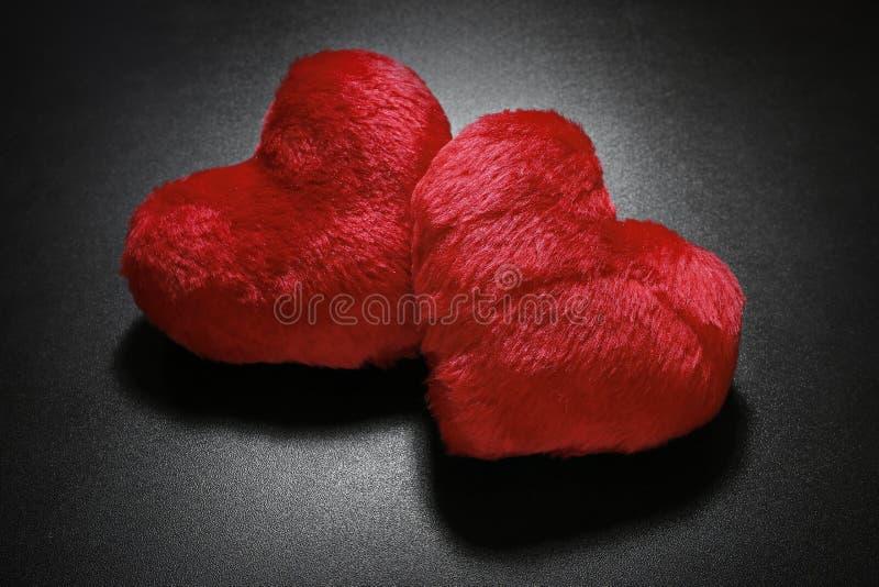 Coeurs rouges pelucheux sur le fond noir photos libres de droits