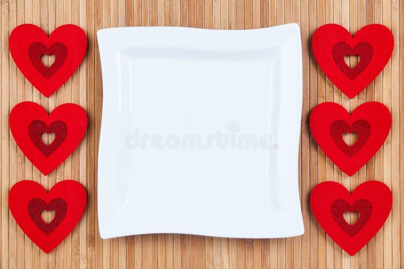 Coeurs rouges sur un fond de bois, plat de place blanche une carte pour le jour du ` s de Valentine photo stock