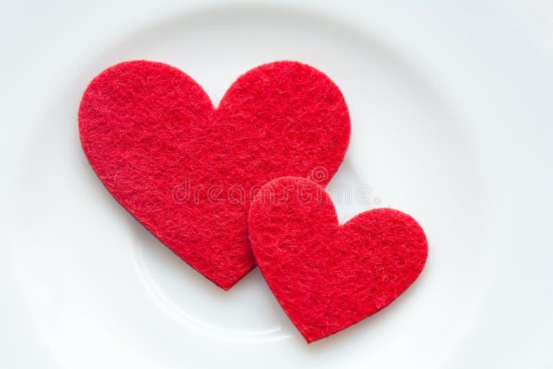 Coeurs rouges sur un plan rapproché de plaque. Saint-Valentin image libre de droits