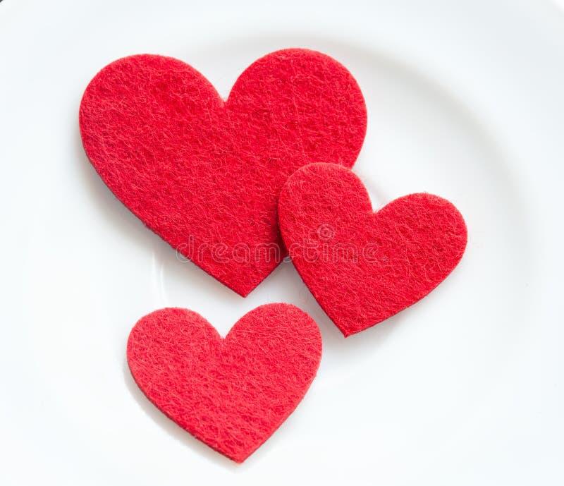 Coeurs rouges sur un plan rapproché de plaque. Saint-Valentin photographie stock libre de droits