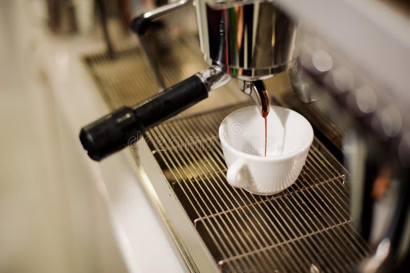 Cofee moderne s'assortissant versant un café frais et aromatique dans une tasse photos libres de droits