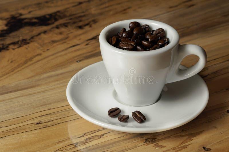 Coffe bönor i espressokopp royaltyfria bilder