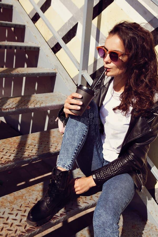 Coffe bevente della bella giovane donna caucasica dalla tazza asportabile nera nel fondo urbano Femmina in blue jeans che si sied fotografia stock libera da diritti