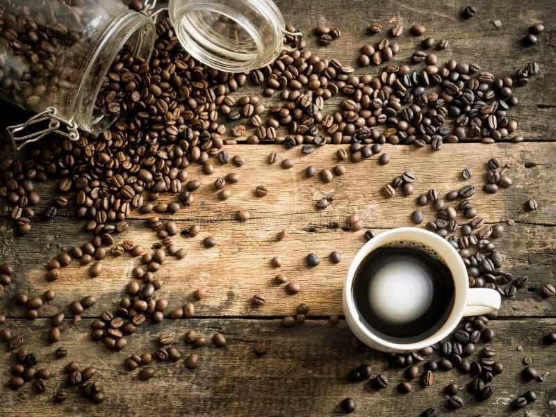 Coffe-Bohnen auf dem Schmutzholz mit Schale stockfotos
