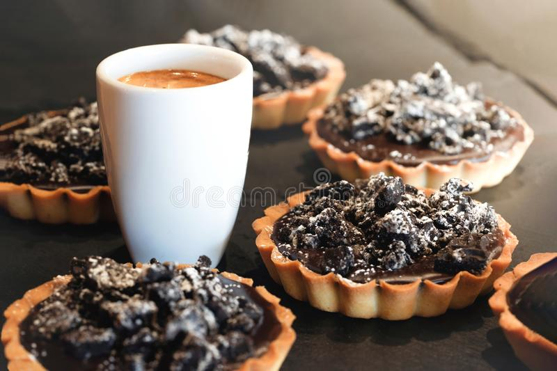 Coffe cup wits delicious chocolate tarts stock photo